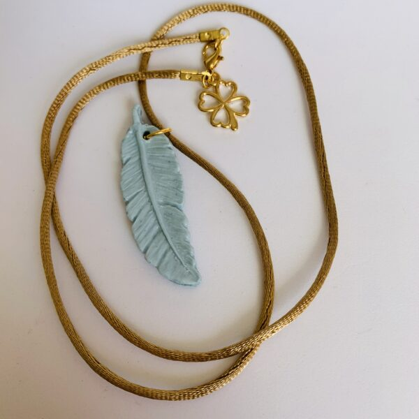 Grace Louise ceramics blue porcelain feather on handmade gold satin cord necklace with lucky charm on the clasp Comes in a beautiful keepsake linen bag Necklace approx 18 inches