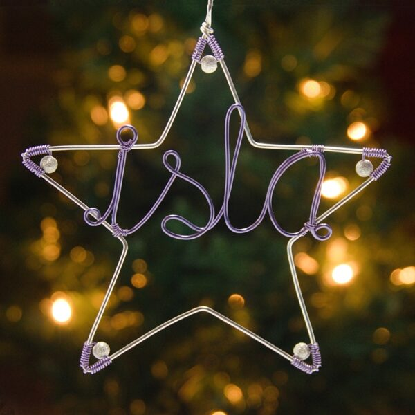 Oruki Design - Personalised Christmas star decoration - silver wire star with lilac wire writing 'isla', fairy lights in background