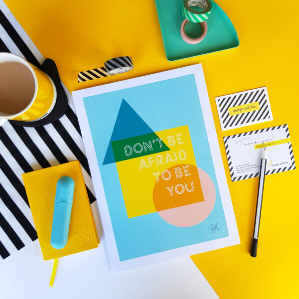 Design and Tea, flat lay of 'Don't be afraid to be you' colourful inspiring typographic print with teal background and shapes and text in colours teal, yellow, green and pink.