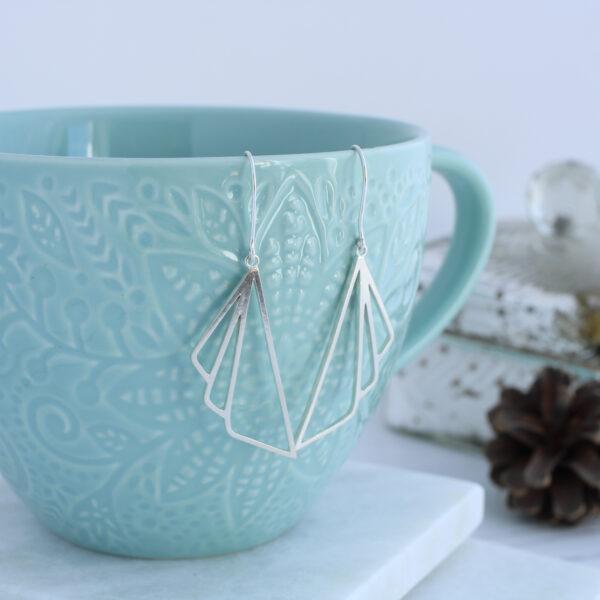Aimi Cairns Jewellery, Silver Art Deco dangle earrings on blue cup