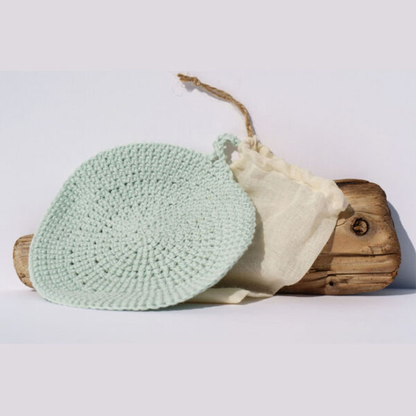 Gemma Thorpe Hand crochet face cloth with muslin bag sat on driftwood