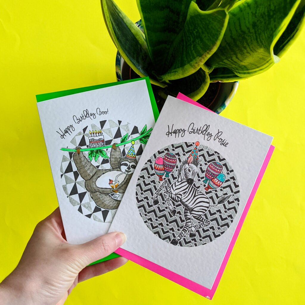 Katie Clement Illustration, Personalised Sloth and Zebra party animals Birthday cards with neon envelopes being held over a yellow background with a potted plant in the background.