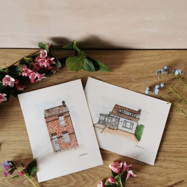 Jessica Sian Illustration, hand drawn and painted portrait of two houses in fineliner pen and watercolour paints. the pieces are on a light wooden table against a pale pink wall with pink flowers around them.
