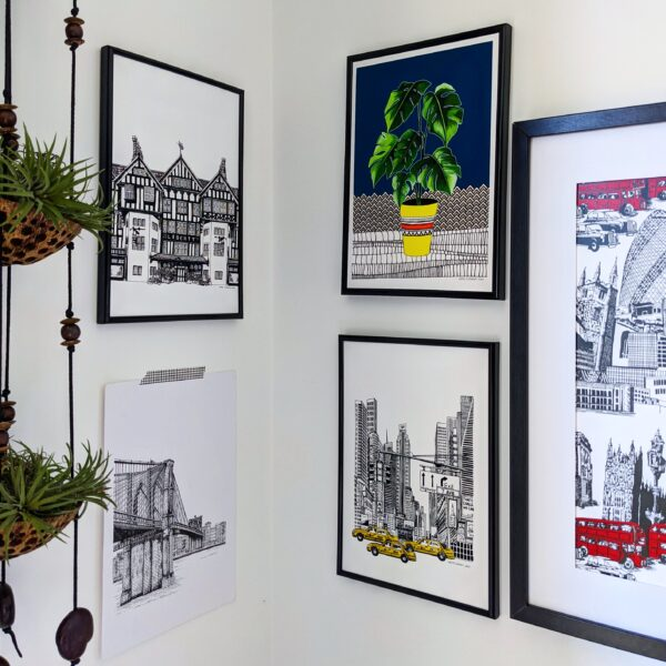 Katie Clement Illustration, Art Print Gallery wall featuring framed Liberty of London, Monstera, Times Square and London Skyline Prints and an unframed Brooklyn Bridge print