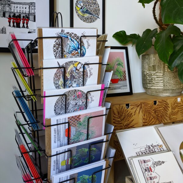 Katie Clement Illustration, Card browser featuring Party Animals birthday cards, and houseplant cards, next to a print browser showing some of the Skyline print collection, with sections of the A5 Palm Print, A5 Blue Tit Print and the London Skyline Screen print framed on the wall.