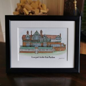 Jessica Sian Illustration, a framed painting of Liverpool Cricket Club Pavilion hand drawn and painted with fineliner pen and watercolour paints with the title Liverpool Cricket Club Pavilion written underneath. The piece is in a black frame with an off white mount and sat on a dark wood table.