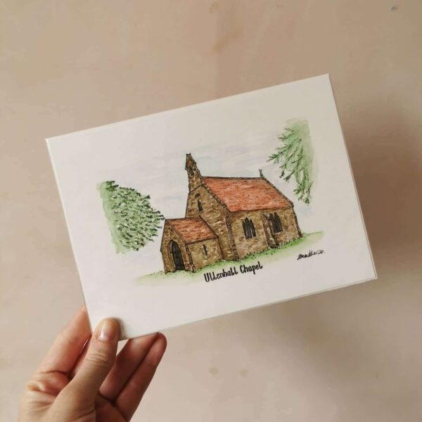 Jessica Sian Illustration, Ullenhall Chapel fineliner drawing and watercolour painting of the chapel with the title Ullenhall Chapel written underneath. The piece is held up against a pale pink wall.
