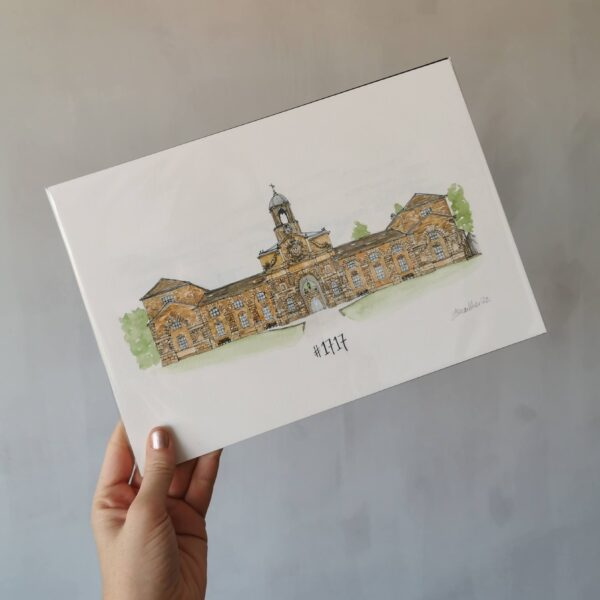 Jessica Sian Illustration, wedding venue illustration in fineliner pen and watercolour paints of Chatsworth Stables with personalised text underneath with the date of the wedding. The piece is in front of a pale grey wall.