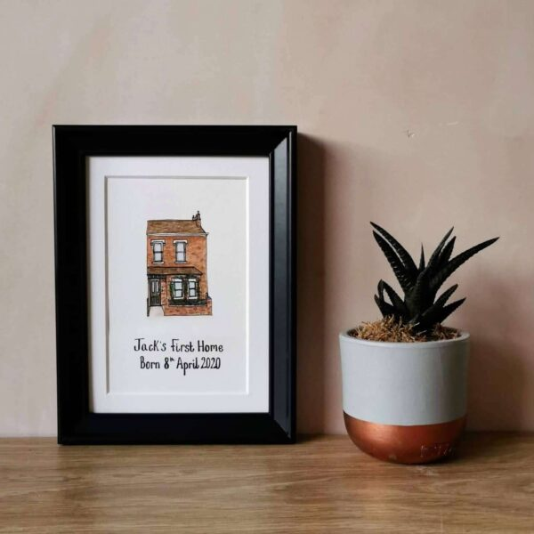 Jessica Sian Illustration, A hand drawn and painted A6 illustration of a house with Jack's first Home and his date of birth written underneath, it is a baby gift. The piece is drawn in fineliner pen and painted with watercolours. The piece is in a black frame with a white mount on a light wood table against a pink wall. A small plant sits next to the frame.