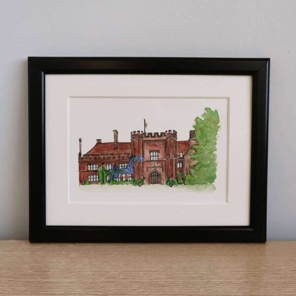 Jessica Sian Illustration, A5 watercolour wedding venue illustration, drawn by hand in pen and painted with watercolours. The piece is framed in a black frame with an off white mount, it sits on a light wooden table against a grey wall.