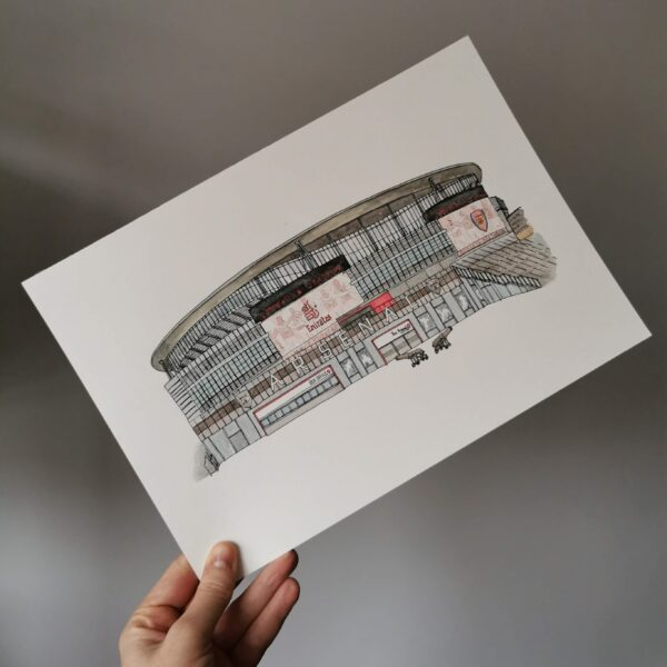 Jessica Sian Illustration, Arsenal stadium drawing and watercolour painting drawn by hand in fineliner pen and then painted with watercolour paints. The piece is being held in front of a grey wall.