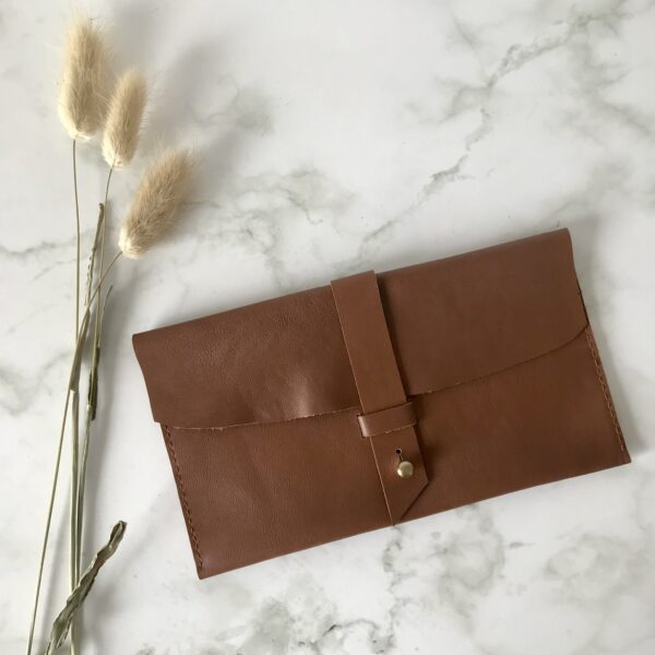 Romy Design Tan Leather Sleeve in fold over envelope style, hand-stitched edges with a slim strap to fasten closed on a copper stud.