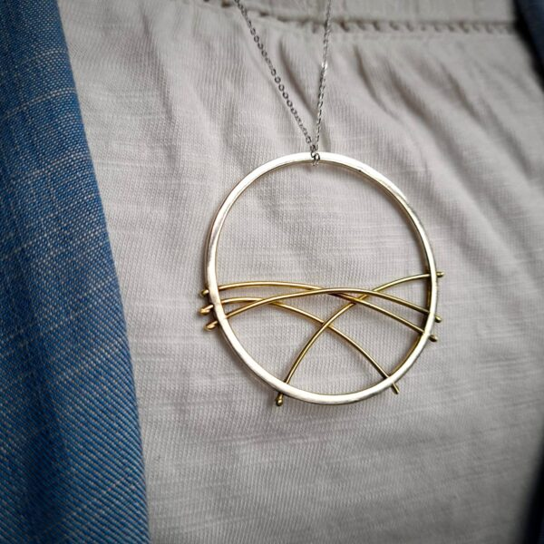 KiJo Jewellery: Geometric Circle Pendant Necklace Close Up Silver circle with brass gold arched wires