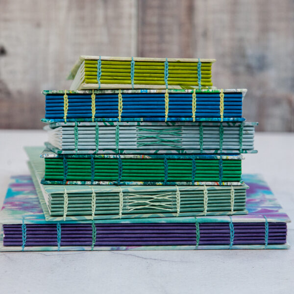 The Eloise Bindery, Stack of colourful hand bound coptic stitch sketchbooks
