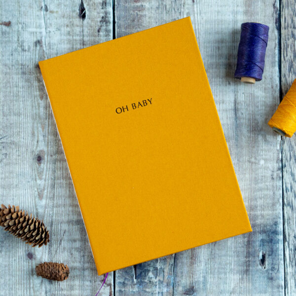 The Eloise Bindery, personalised yellow hand bound journal with 'Oh Baby' text