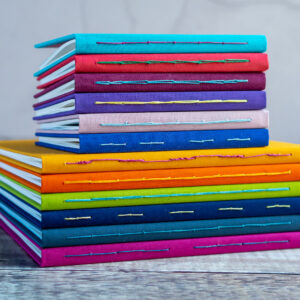 The Eloise Bindery, Stack of colourful hand bound fabric journals with exposed stitching