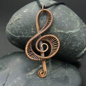 Oruki Design, Wire Woven Copper Treble Clef Pendant on grey stones against black background