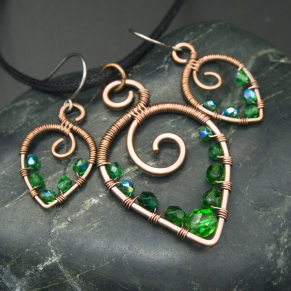 Oruki Design, hammered copper leaf shaped copper pendant and matching earrings with green glass beads, on grey stone
