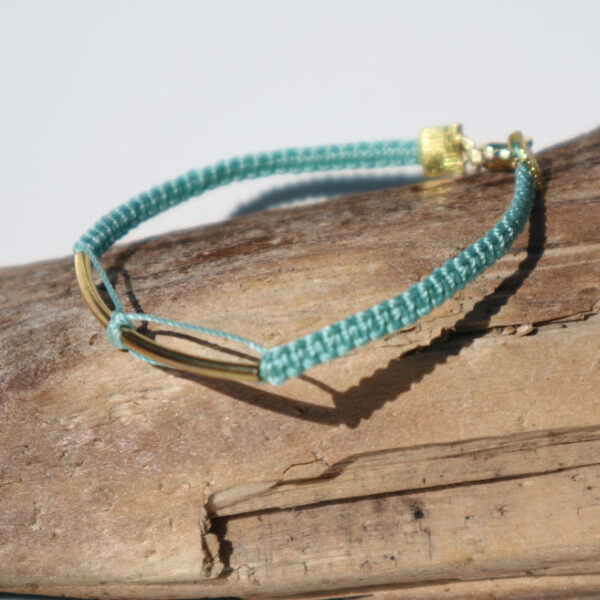 Gemma Thorpe macrame bracelet in teal yarn with gold coloured bar sat on driftwood