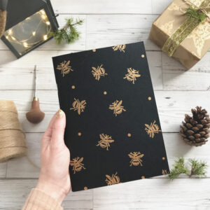 black beautiful bees sketchbook with gold bees hand printed, pine needles and pine cone in background