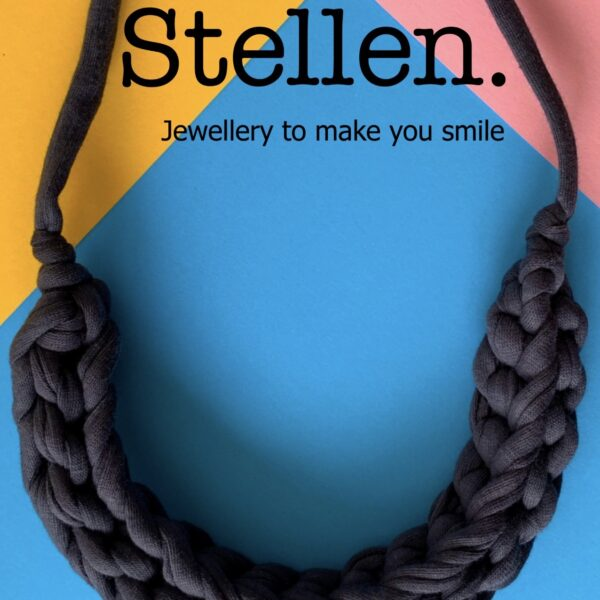 Stellen curve necklace in Anthracite Grey on a blue pink and yellow background