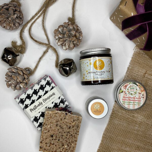 That Refill Place, Plastic Free Facial Pamper Gift Set, containing soap, lip balm, facial cleasning balm, facial moisturiser, reusable cotton pads, pine cones and bells on a string