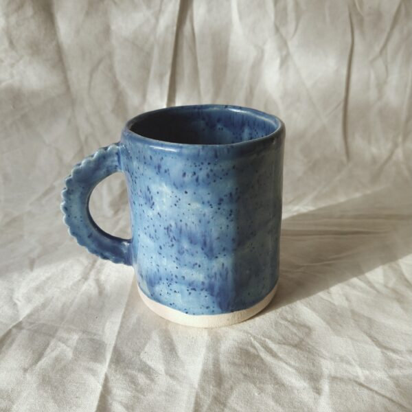 Victoria Ceramics, handmade stoneware mug with glazed in speckled blue and a scalloped handle