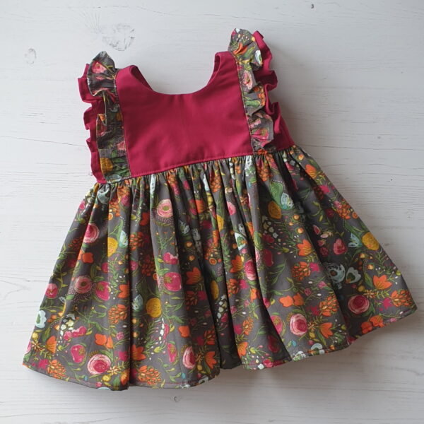 Baby dress in autumn floral fabric on a warm grey background with a contrasting sangria pink bodice with double over the shoulder frills in both fabrics