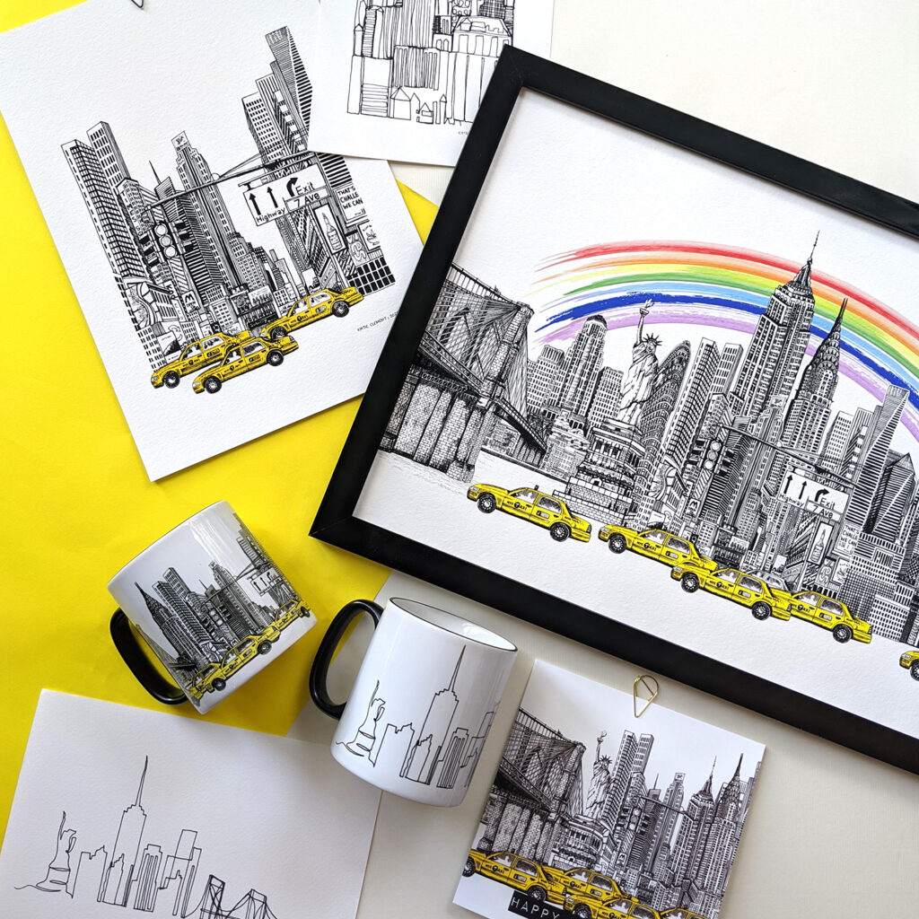 New York Cityscape Fine Art Collection laid flat against a white and yellow background. Including the Rainbow Edition A3 Skyline Print, A4 Times Square Print, the New York Skyline and New York Just a Line Mugs, a5 Just A line Print and New York Birthday Card