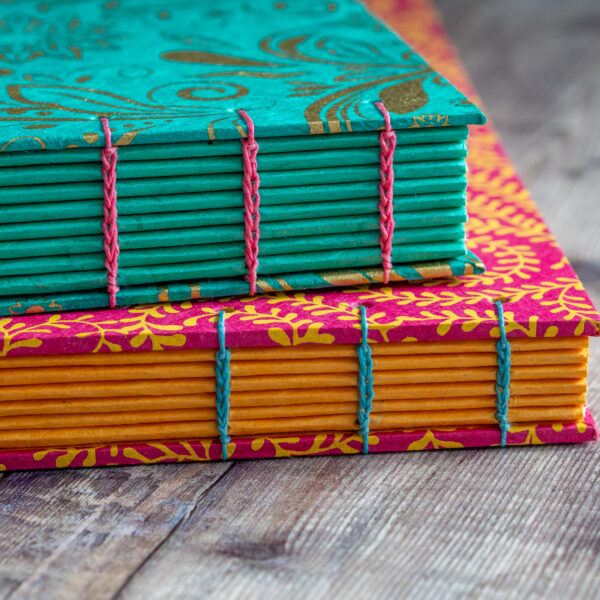 The Eloise Bindery, hand bound coptic stitch sketchbooks with decorative floral covers in turquoise, pink and yellow