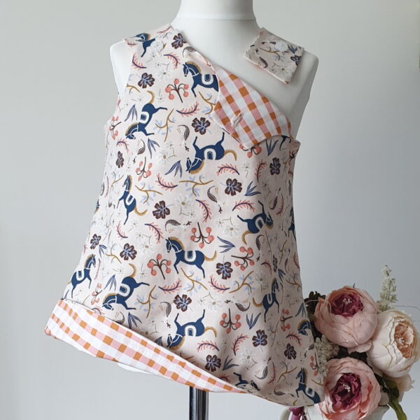 Girls reversible pinafore dress with shoulder button fastening with blue horses on peach floral background on one side and peach and cream check on the reverse