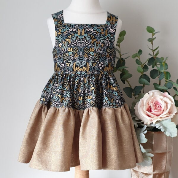 Girls dress with full gathered tiered skirt. Bodice and top tier in green and gold metalic floral fabric with the botton skirt tier in metallic gold linen