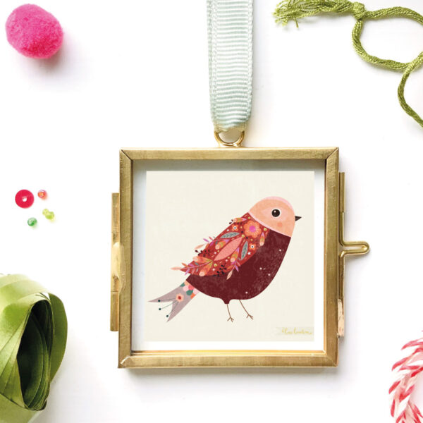 miniature print of a little red birdie illustration by bee brown in a brass and glass frame surrounded by beads, sequins, green ribbon and pompom
