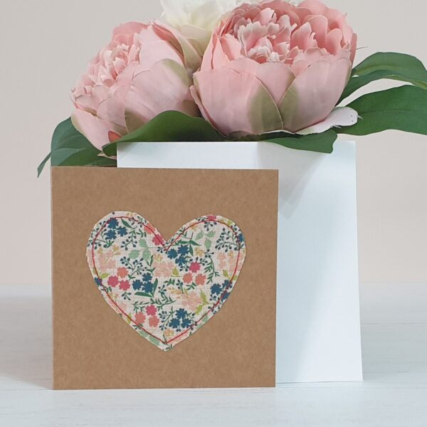 Small brown Kraft card with a ditsy floral fabric heart in blues reds greens and oranges machine sewn on with red thread