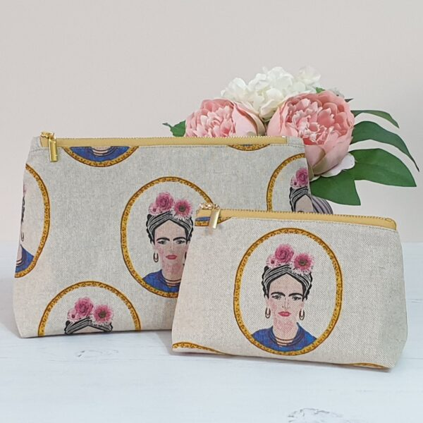 Large and medium size zip bag with a polished gold zip in fabric with a portrait of Frida Kahlo printed on