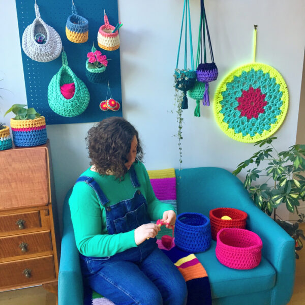 Clare sitting on a sofa surrounded by crochet