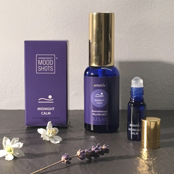 Emotiv Aromatherapy MIDNIGHT CALM Deep relaxation aromatherapy. Image shows pillow mist and roll on blend for deep relaxation before restful sleep. Blue glass bottle with gold metal cap and stunning purple labels.