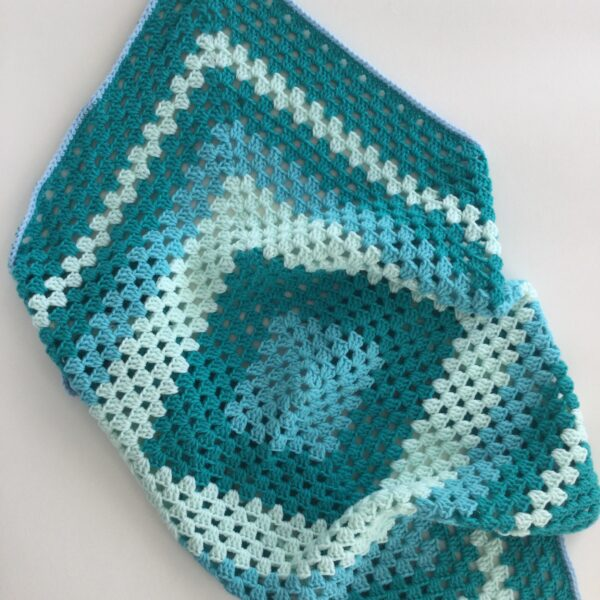 A calming green toned crochet baby blanket, perfect to tuck around the little one in the car seat