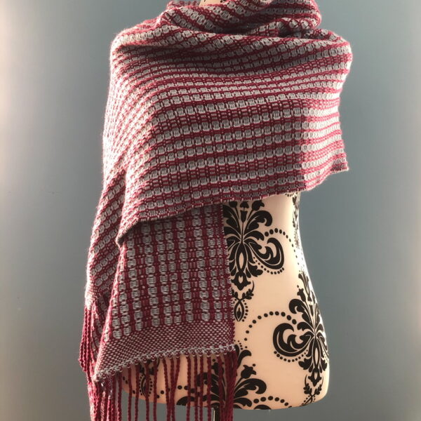 Woven wrap in wine red and blue colours with a pattern that results in it being predominantly blue on the reverse