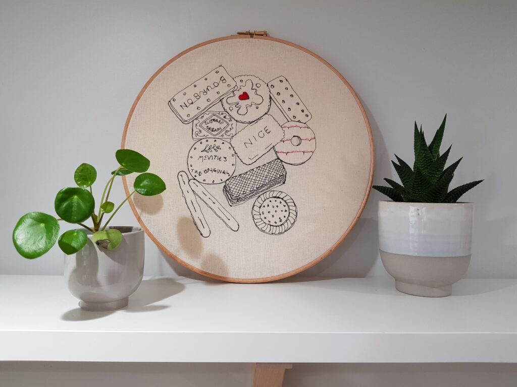 """Gemma Rappensberger Teatime Treats embroidered illustration using free motion machine embroidery of favourite teatime biscuits in black cotton thread with hand embroidery details on calico in a 12"""" wooden embroidery hoop"""
