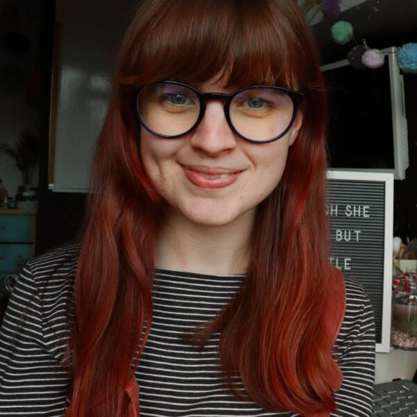 Photo of Brown Paper Festival founder Megan, she has red brown hair and is wearing a grey and white stripe top and blue glasses
