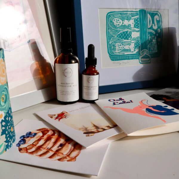 A selection of Brown Paper Festival stallholder products including greeting cards, facial oils and art