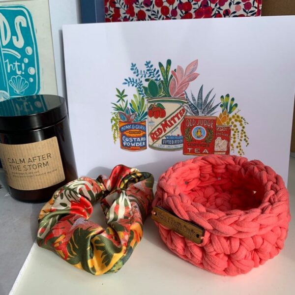 A selection of Brown Paper Festival stallholders products including a coral crochet basket, a floral silk scrunchie, a candle and artwork