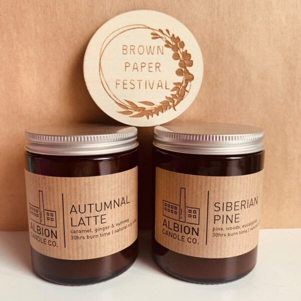 Two candles from Albion Candle Co with the Brown Paper Festival logo
