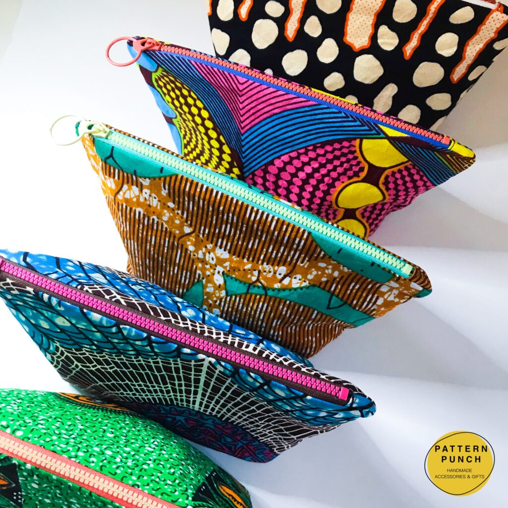 A selection of zip up bags in a variety of African wax print fabrics. Pattern Punch