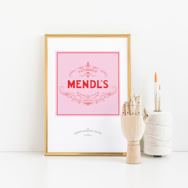 Gothenburg Print, The Grand Budapest Hotel Mendl's Box print in a gold frame next to a wooden artists hand and paint brushes