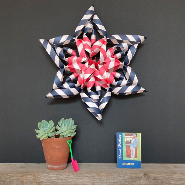 Art Star Folded Paper Star Kit David, a striped blue, white and red star on a dark grey wall above a shelf