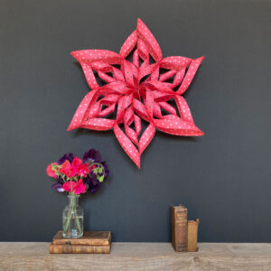 Art Star folded paper star kits pink spotted star Sonia on a dark grey wall above a shelf