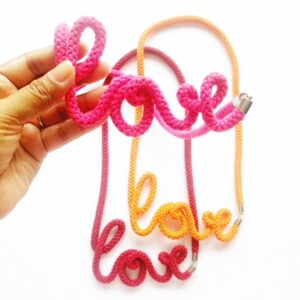 A hand is holding a cotton necklace saying the word 'love' in Pink and you can see two same necklaces in orange and maroon in the white background