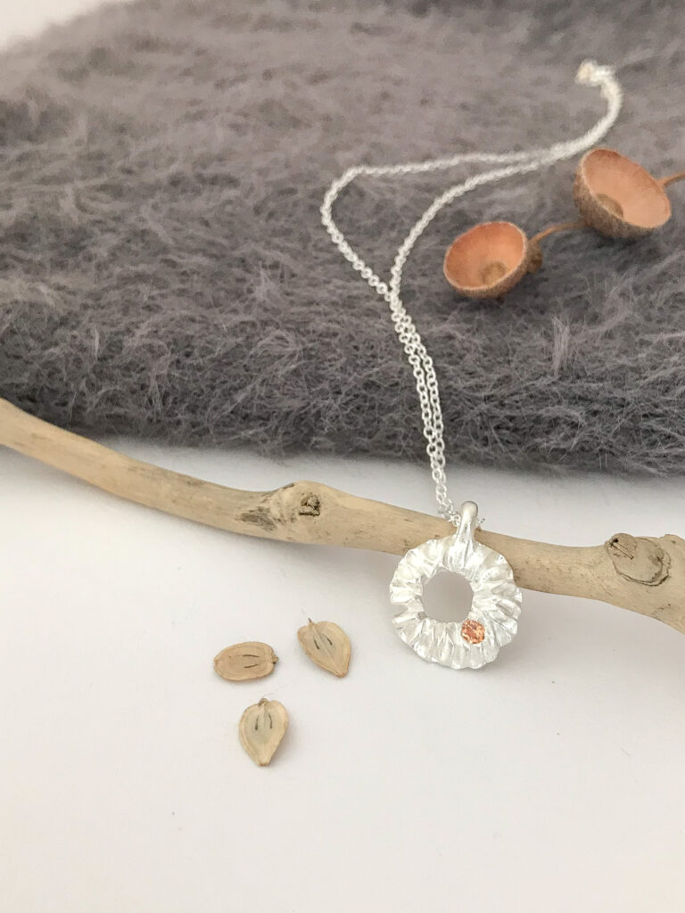 gail ann jewellery,fine silver organic shaped pendant round pendant with central hole and champagne coloured gem on a dainty sterling silver chain